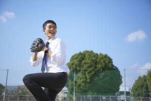 青空の下で野球をするスーツ姿の男性の写真素材 [FYI04729262]