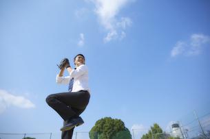青空の下で野球をするスーツ姿の男性の写真素材 [FYI04729263]