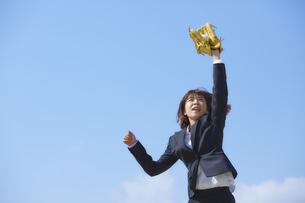青空の下でグローブをつけた手を伸ばすスーツの女性の写真素材 [FYI04729265]