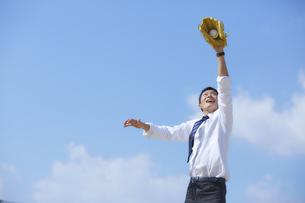 青空の下でグローブをつけた手を伸ばすスーツの男性の写真素材 [FYI04729266]