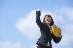 青空の下でボールを投げようとするスーツの女性の写真素材 [FYI04729267]