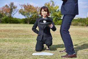 芝生で野球をする男女の写真素材 [FYI04729279]