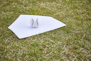 芝生の上のホームベースと野球ボールの写真素材 [FYI04729283]