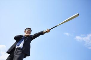 青空の下でバットを構えるスーツの男性の写真素材 [FYI04729284]