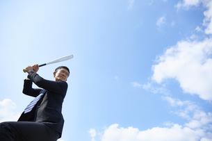 青空の下でバットを構えるスーツの男性の写真素材 [FYI04729285]