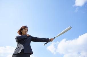 青空の下でバットを構えるスーツの女性の写真素材 [FYI04729286]