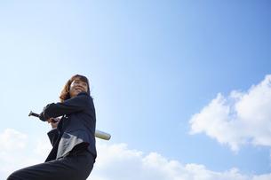 青空の下でバットを構えるスーツの女性の写真素材 [FYI04729287]