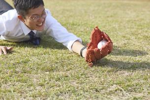 野球ボールをダイビングキャッチするスーツの男性の写真素材 [FYI04729288]
