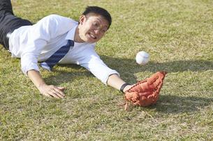 野球ボールをダイビングキャッチするスーツの男性の写真素材 [FYI04729289]