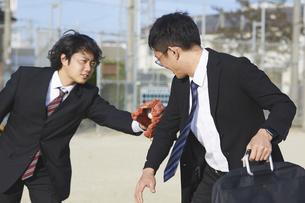タッチアウトをするスーツの男性2人の写真素材 [FYI04729291]