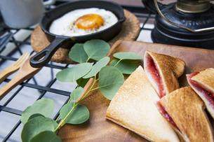 目玉焼きと苺ジャムのホットサンドのアウトドアな朝ごはんのイメージの写真素材 [FYI04729322]