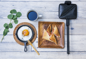 目玉焼きと苺ジャムのホットサンドのアウトドアな朝ごはんのイメージの写真素材 [FYI04729324]