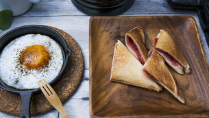 目玉焼きと苺ジャムのホットサンドのアウトドアな朝ごはんのイメージの写真素材 [FYI04729328]