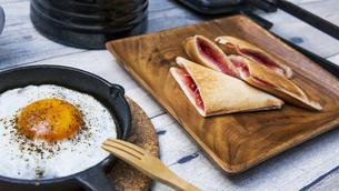 目玉焼きと苺ジャムのホットサンドのアウトドアな朝ごはんのイメージの写真素材 [FYI04729330]