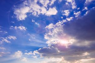 【自然風景】青空の雲の隙間から太陽光が差し込む様子 レンズフレア 背景素材の写真素材 [FYI04729572]