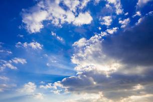 【自然風景】青空の雲の隙間から太陽光が差し込む様子 光芒 背景素材の写真素材 [FYI04729573]
