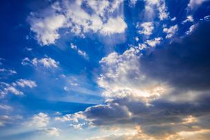 【自然風景】青空の雲の隙間から太陽光が差し込む様子 光芒 背景素材の写真素材 [FYI04729574]