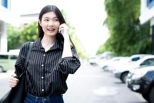 歩きながら携帯電話で話す若い女性の写真素材 [FYI04729612]