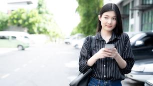 笑顔で携帯電話を操作しながら歩いている若い女性の写真素材 [FYI04729613]