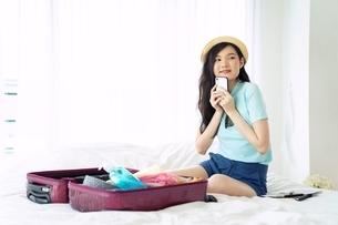 楽しそうに旅行の荷造りをしている若い女性の写真素材 [FYI04729614]