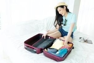 楽しそうに旅行の荷造りをしている若い女性の写真素材 [FYI04729615]