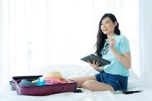 荷造りしながら旅行のプランを計画している若い女性の写真素材 [FYI04729618]