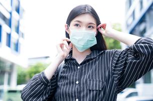 フェースマスクを調節している若い女性の写真素材 [FYI04729625]