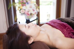 エステサロンのベッドに横たわる女性の写真素材 [FYI04729658]
