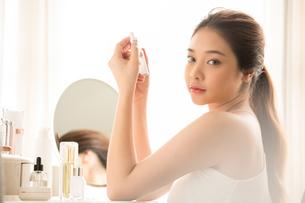 メイクアップとスキンケアをしているきれいな若い女性の写真素材 [FYI04729973]