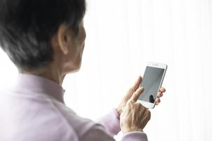 スマートフォンを操作する高齢者の女性の後ろ姿の写真素材 [FYI04730056]