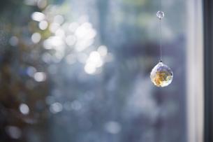 美しいガラスのクリスタルのサンキャッチャーの飾りがある窓辺の写真素材 [FYI04730098]