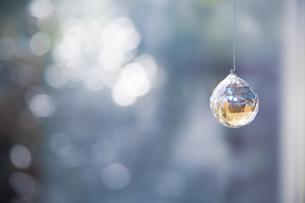 美しいガラスのクリスタルのサンキャッチャーの飾りがある窓辺の写真素材 [FYI04730099]