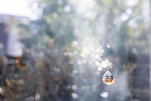 美しいガラスのクリスタルのサンキャッチャーの飾りがある窓辺の写真素材 [FYI04730100]