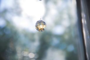 美しいガラスのクリスタルのサンキャッチャーの飾りがある窓辺の写真素材 [FYI04730104]