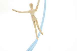 落ちそうになりながら綱渡りをするデッサン人形の写真素材 [FYI04730221]