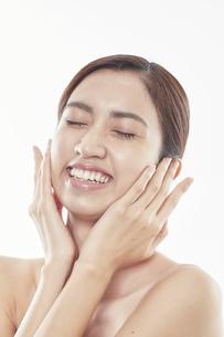 頬に手を添える日本人女性のビューティイメージの写真素材 [FYI04730370]