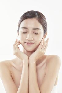 頬に手を添える日本人女性のビューティイメージの写真素材 [FYI04730371]
