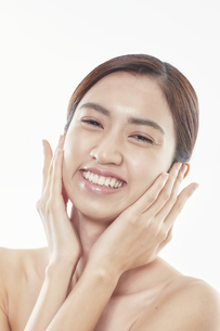 頬に手を添える日本人女性のビューティイメージの写真素材 [FYI04730372]