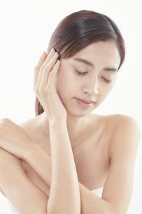 頬に手を添える日本人女性のビューティイメージの写真素材 [FYI04730373]
