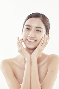 頬に手を添える日本人女性のビューティイメージの写真素材 [FYI04730377]