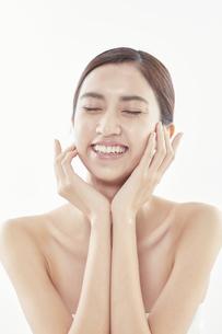 頬に手を添える日本人女性のビューティイメージの写真素材 [FYI04730384]