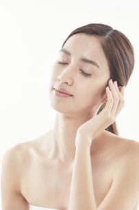 頬に手を添える日本人女性のビューティイメージの写真素材 [FYI04730385]
