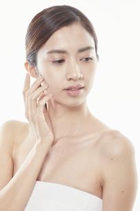 頬に手を添える日本人女性のビューティイメージの写真素材 [FYI04730386]
