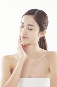 頬に手を添える日本人女性のビューティイメージの写真素材 [FYI04730387]