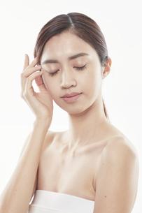 頬に手を添える日本人女性のビューティイメージの写真素材 [FYI04730389]