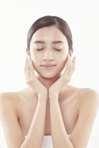 頬に手を添える日本人女性のビューティイメージの写真素材 [FYI04730390]