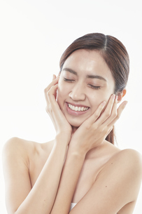 頬に手を添える日本人女性のビューティイメージの写真素材 [FYI04730392]