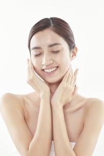 頬に手を添える日本人女性のビューティイメージの写真素材 [FYI04730393]