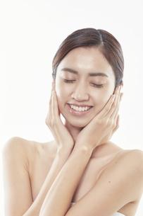 頬に手を添える日本人女性のビューティイメージの写真素材 [FYI04730394]