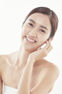 頬に手を添える日本人女性のビューティイメージの写真素材 [FYI04730395]